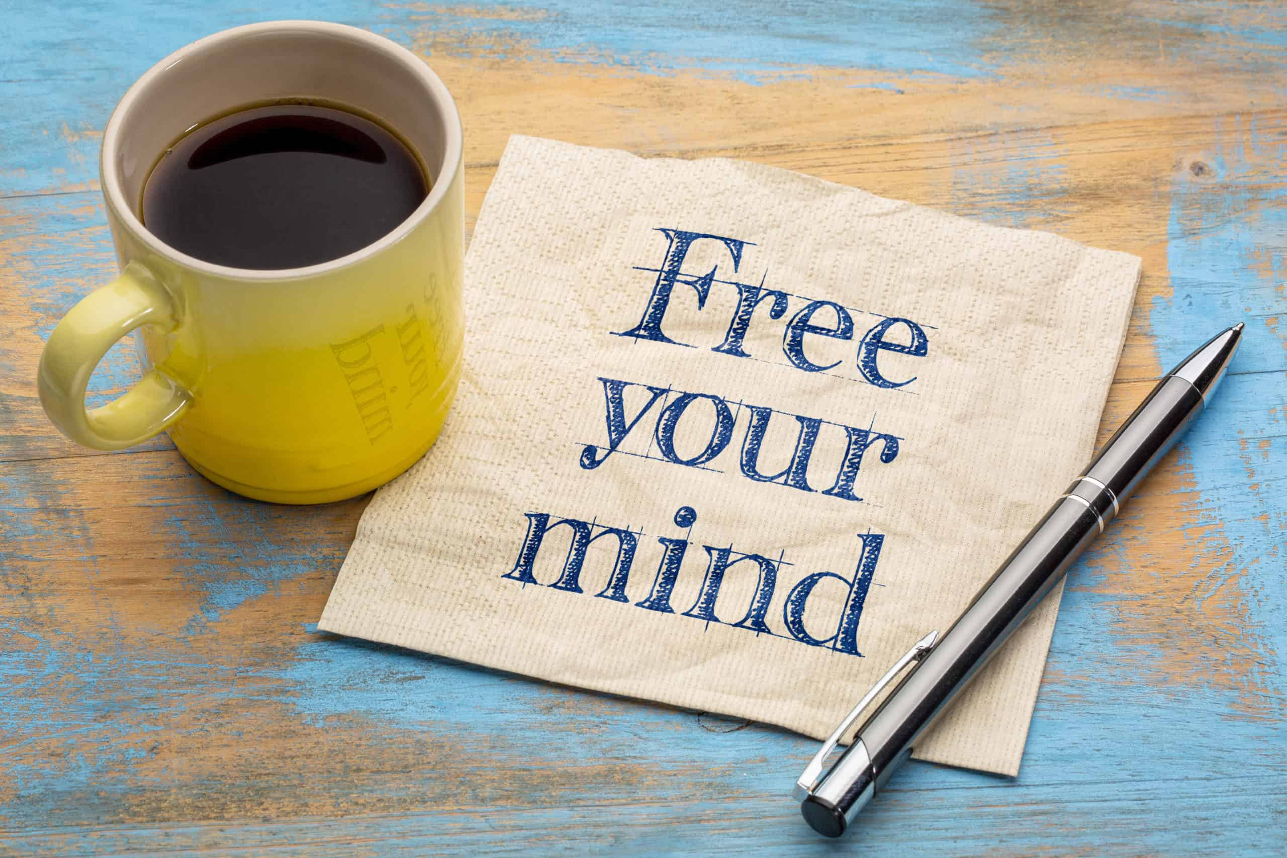 free your mind reminder note - handwriting on a napkin with a cup of coffee